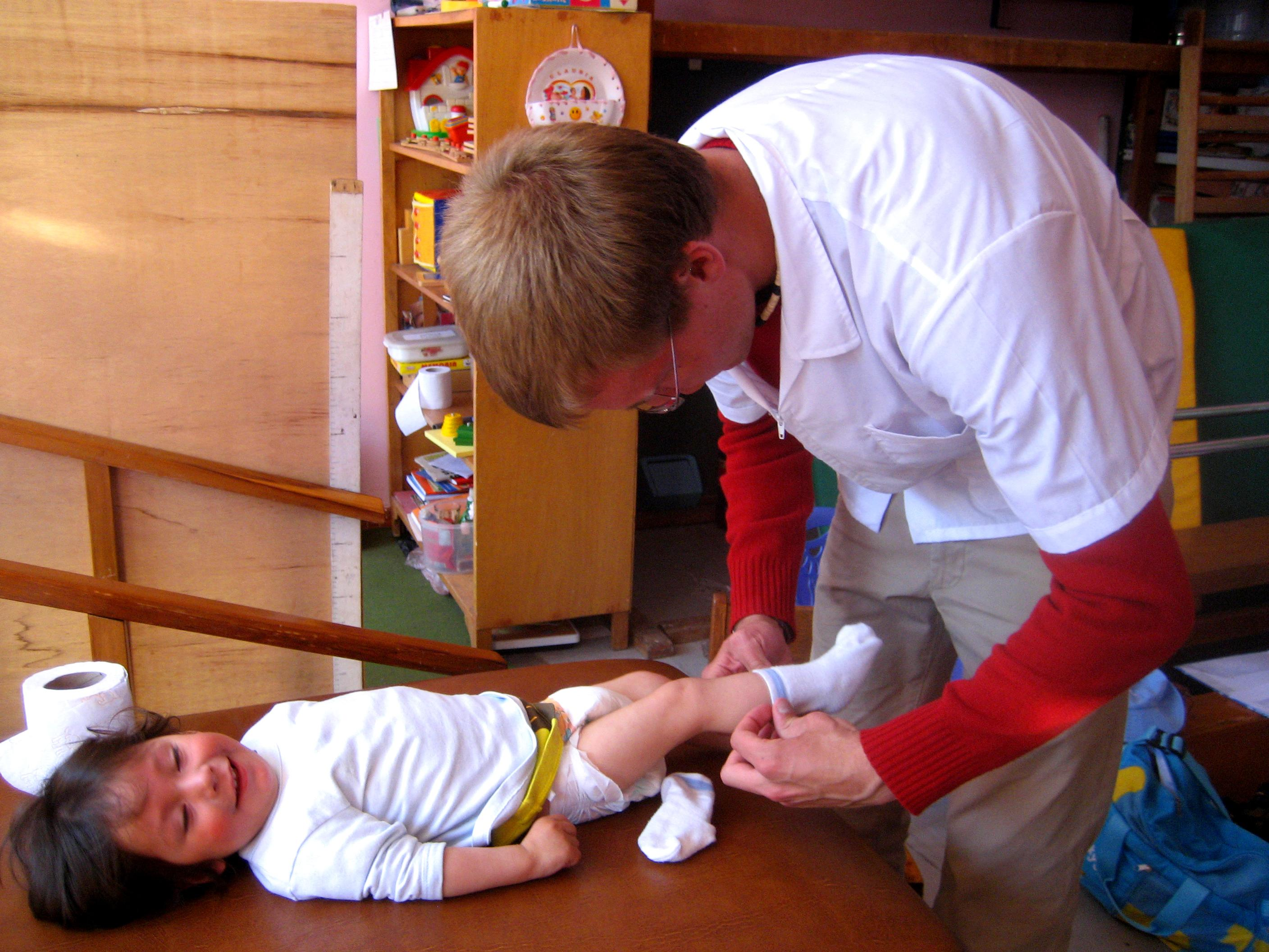 A male intern from Projects Abroad is pictured dressing a baby in new clothes as part of his midwifery internship in Peru.